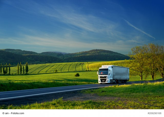 White truck driving on the asphalt road in a rural landscape with forested mountains in the background